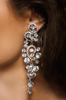 Ухо и красивая большая серьга с множеством драгоценных камней