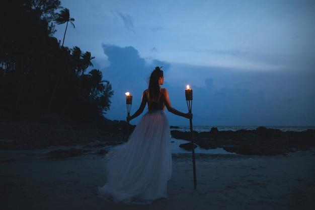 美しいウェディングドレスの花嫁はビーチでたいまつを保持しています。