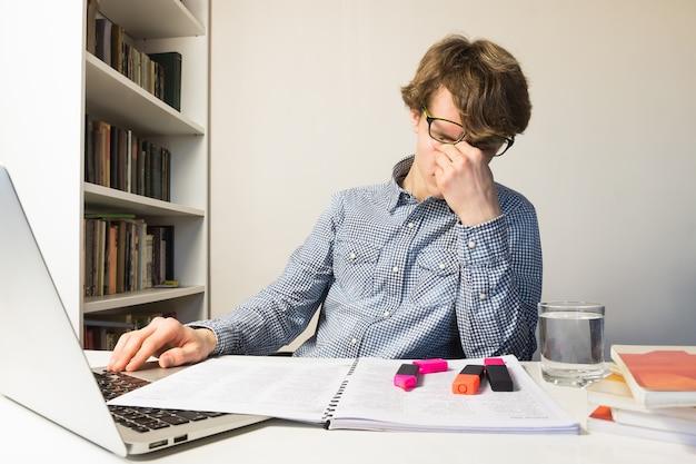疲れた目をこすりながら男性の人が学校や仕事のプロジェクトの締め切りを満たす。