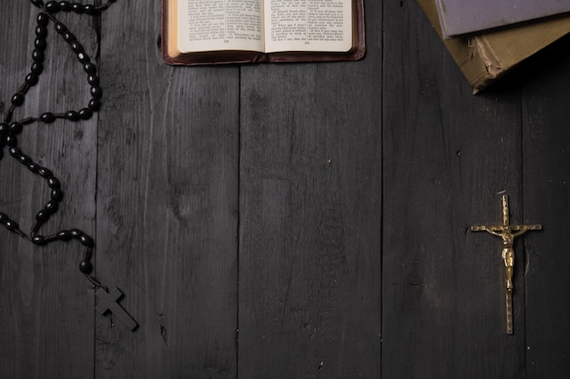 暗いテーブル、トップビューで聖書と十字架の本を開きます。新約聖書の十字架とロザリオの古い黒い表面のフラットレイアウトイメージ