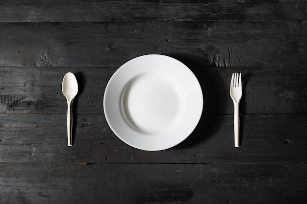 空の白いボウル、フォーク、スプーン黒の木製テーブル、トップビュー。ダイエットコンセプト:暗い素朴な表面にきれいなキッチン料理のフラットレイアウト