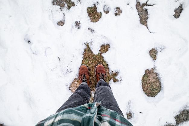 雪の中の足、視点。冬の散歩で暖かいカジュアルな服装の人のショットの真上