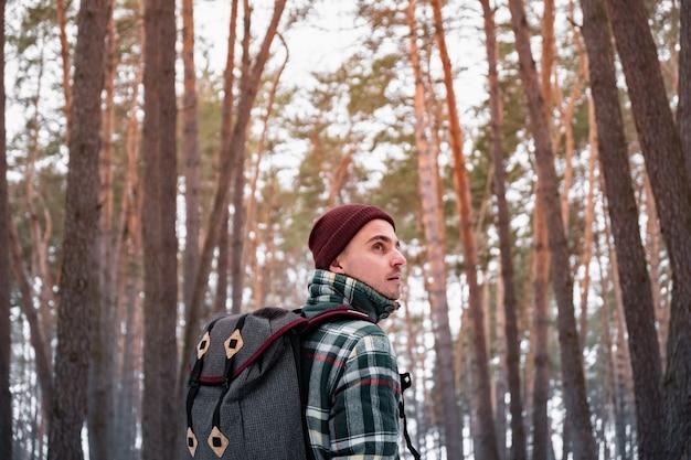 冬の森で男性の人をハイキングします。美しい雪に覆われた森の中を歩いて市松模様の冬シャツの男