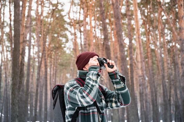 写真を撮る冬の森で男性の人をハイキングします。美しい雪に覆われた森の中で市松模様の冬シャツの男は、古いフィルムカメラを使用します