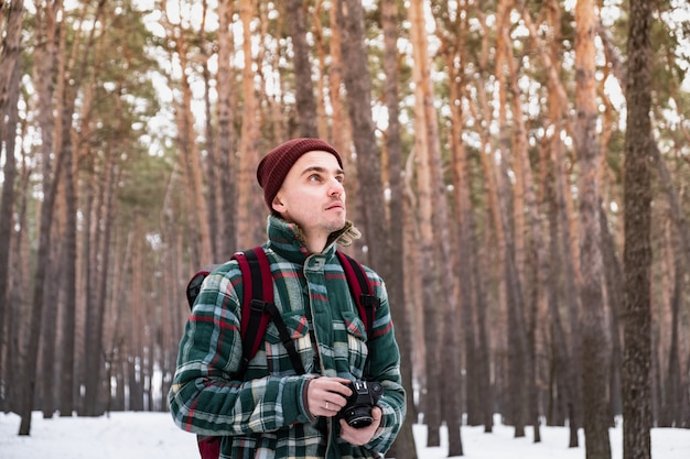 写真を撮る冬の森で男性の人をハイキングします。古いフィルムカメラで美しい雪に覆われた森の中で市松模様の冬シャツの男