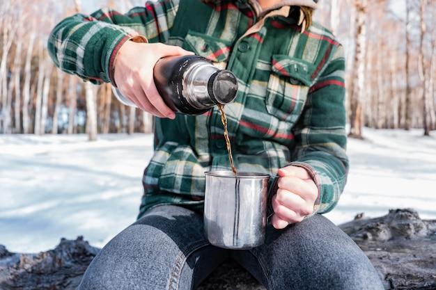 キャンプ場で魔法瓶から熱い飲み物を注ぐ。ハイキング旅行中に暖かくなる冬の森の人