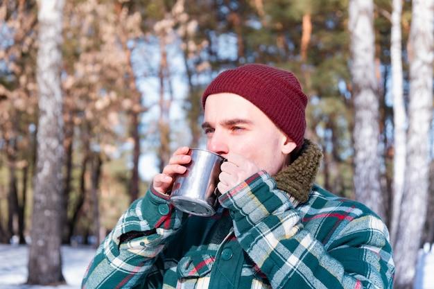 男性は、雪に覆われた冬の森のカップから飲みます。市松模様のシャツを着た男は屋外でコーヒーのカップを保持します