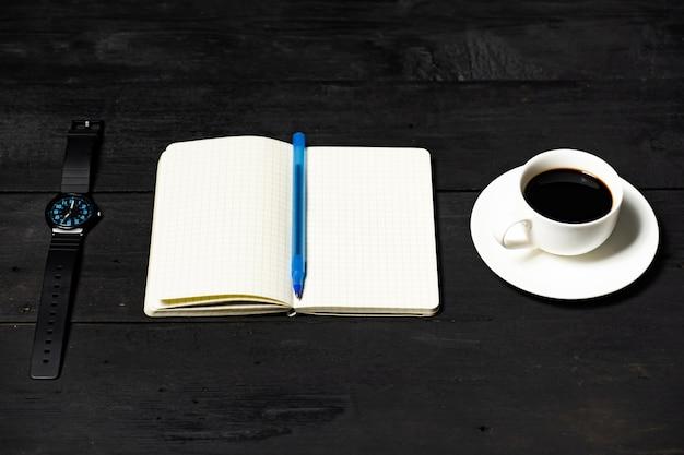 時間管理の概念。黒い木製の表面にあるメモ帳、コーヒーカップ、機械式時計
