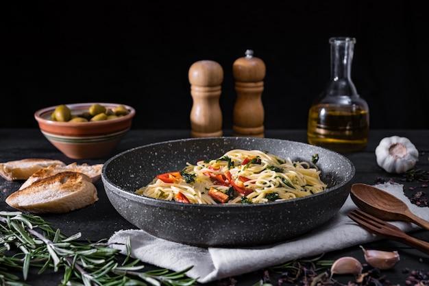 調理されたイタリアのパスタのパン。黒の素朴な表面に野菜とオリーブの伝統的なスパゲッティの食事