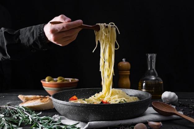 鍋からイタリアンパスタを提供しています。黒の素朴な表面に野菜とオリーブの伝統的なスパゲッティの食事