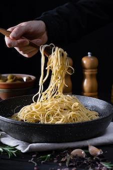 鍋から伝統的なイタリアのパスタを提供しています。低キーで撮影したスプーンとフォークでスパゲッティを取って男性の手