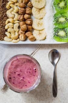 健康的なローフードの朝食とスムージーボウルの新鮮な食材。キウイ、ココナッツフレーク、カシューナッツ、ヘーゼルナッツ、上から撮影、アサイボウルの材料