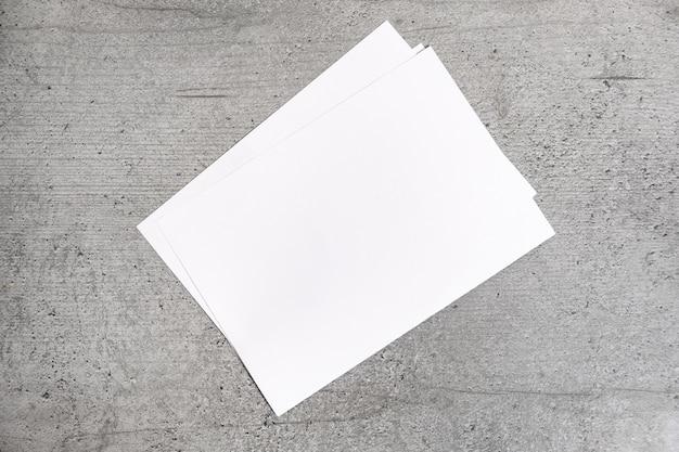 灰色の背景の空白の紙のシート。セメント様式化されたテーブルの上に敷設するホワイトペーパーのトップビュー