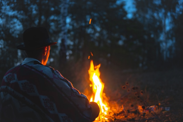 夜のキャンプファイヤーでの静かな時間。森の中の火のそばに座っているポンチョと帽子の男