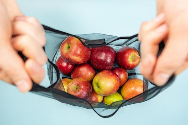 Держа многоразовый шнурок, полный яблок.
