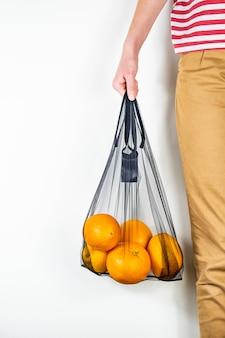 Держа многоразовую сумку, полную апельсинов.