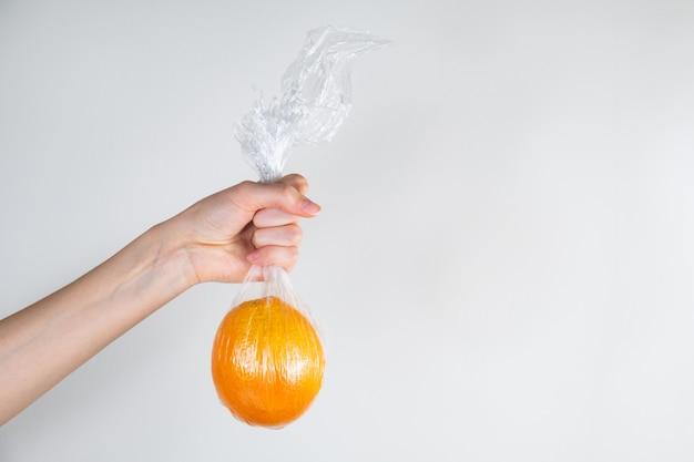 Концепция чрезмерного использования пластика: оранжевый в полиэтиленовой пленке держится в руке.