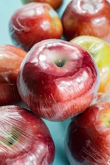 Концепция чрезмерного использования пластика: свежие яблоки в кухонной упаковке.