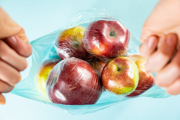 過度のプラスチック使用の概念:ビニール袋に包まれたキッチンの新鮮なリンゴ。