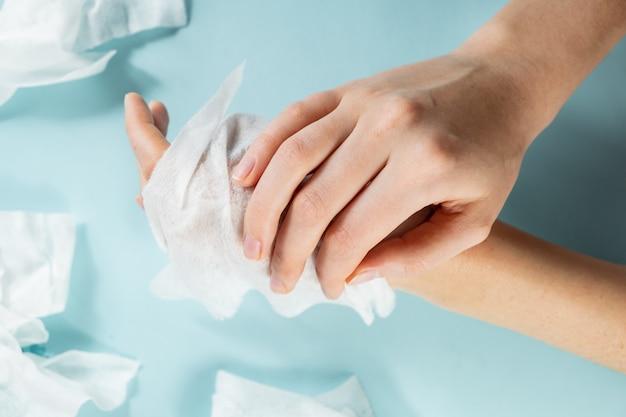 不合理なプラスチック汚染の概念:ウェットワイプの過剰使用。クローズアップビューの手は、多くの湿った組織できれいになります