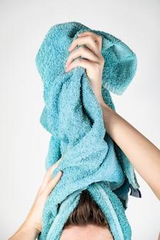 タオルで髪を乾かす女性。手動ヘアドライヤーにバスタオルを使用して女性のクローズアップ