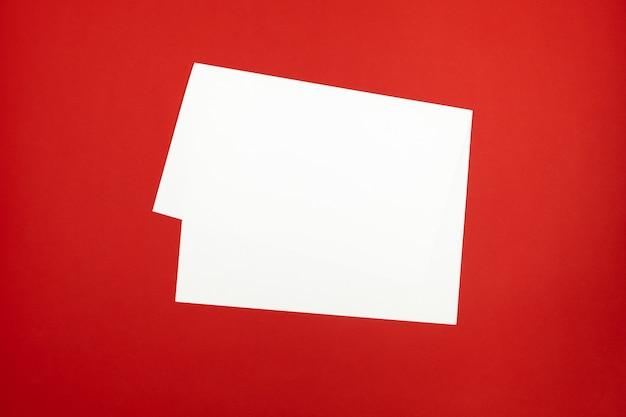明るい赤の背景の空白の紙のシート。鮮やかな色のテーブルの上に敷設された曲げられたホワイトペーパーの平面図
