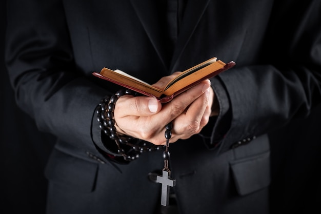 十字架を押しながら新約聖書の本を読んで黒い服を着たキリスト教の司祭の手。宗教的な人は聖書を学び、祈りのビーズ、控えめなイメージを保持します