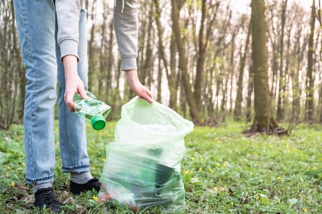 プラスチックごみの森の清掃。人は森の中でペットボトルを拾います、プラスチック意識運動の概念。