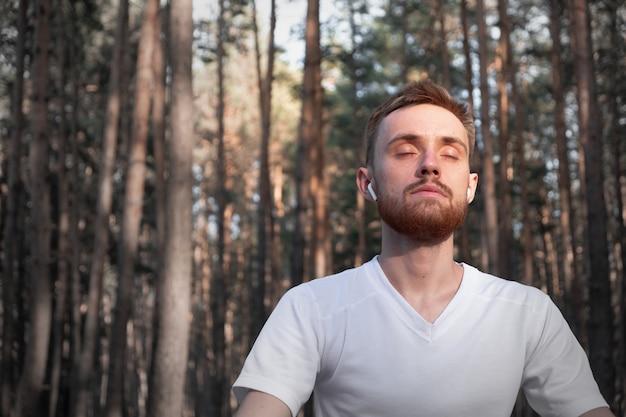 Активный мужчина сидит в сосновом лесу с закрытыми глазами и наслаждается медитацией на природе