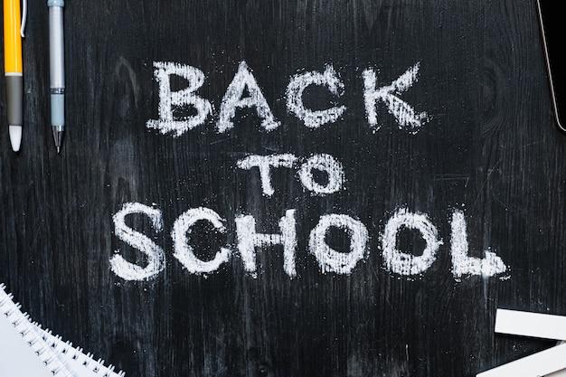 Обратно в школу фраза написана на доске из черного дерева