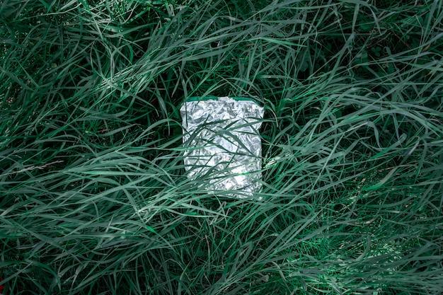 Полиэтиленовый пакет в зеленой траве, концепция загрязнения природы. кусок пластикового мусора (пустой пакет с едой) выбрасывают на газон