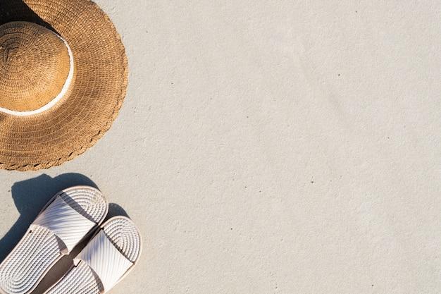 夏の休暇の概念:ビーチスリッパときれいな砂の帽子。海岸に似た自然なコピースペースを持つ海辺の休日のアクセサリーの平面図