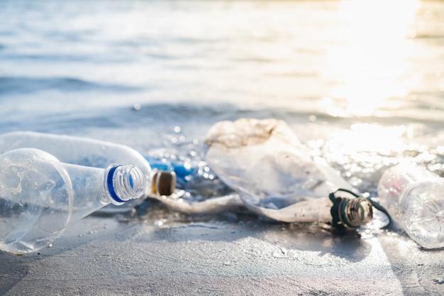 Пустые пластиковые бутылки на пляже, побережье и концепция загрязнения воды