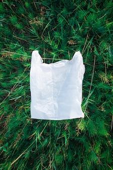 Полиэтиленовый пакет в зеленой траве, концепция загрязнения природы.