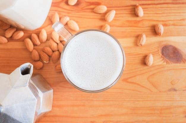 Стакан миндального молока и кофе пивовар на деревянный стол