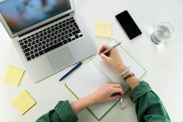 メモ帳とラップトップコンピューターで机で働く