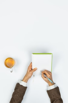 メモ帳で書く、トップビュー。垂直コピースペースと白い背景のコピー本でメモを取る男性の手