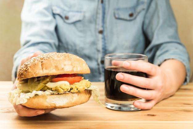 Вегетарианский бургер и стакан безалкогольного напитка в руках