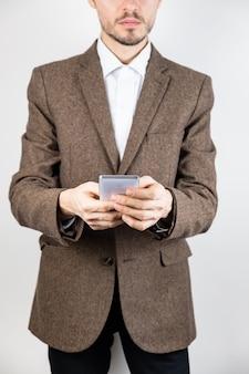 携帯電話でツイードジャケットの男。ビジネス服の男性人は技術、白い背景で詳細なビューを使用します