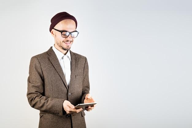 タブレットコンピューターでツイードジャケットの男の笑みを浮かべてください。流行に敏感なスタイルの服の男性人は技術を使用して、白い背景で撮影スタジオ