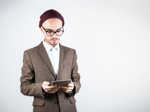 タブレットコンピューターでツイードジャケットの深刻な男。流行に敏感なスタイルの服の男性人は技術を使用して、白い背景で撮影スタジオ