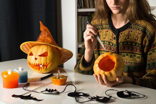 女の子が自宅でハロウィーンのカボチャを彫る