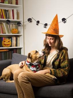 Молодая женщина и ее собака на диване в гостиной, одетый для хэллоуина