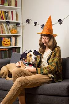 Молодая женщина с ее домашним животным на диване в гостиной, одетый для хэллоуина