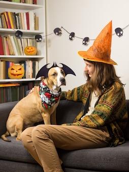 Молодая женщина в шляпе ведьмы хэллоуин сидеть с ее собаку, одетую для домашней вечеринки