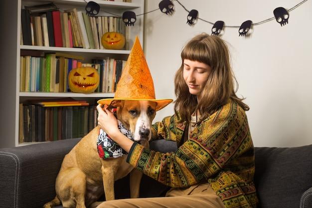 Молодая женщина одевает собаку как ведьма на хэллоуин