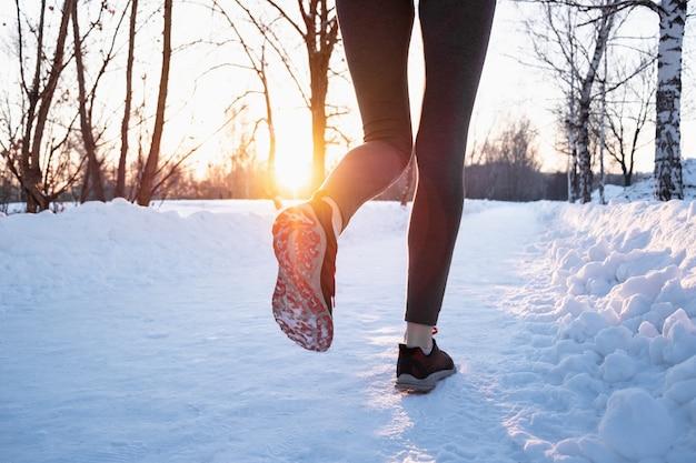 冬のコンセプトで屋外ジョギング。美しい寒い日に雪道に沿って走っている女性の足、レンズフレアで太陽を撃った