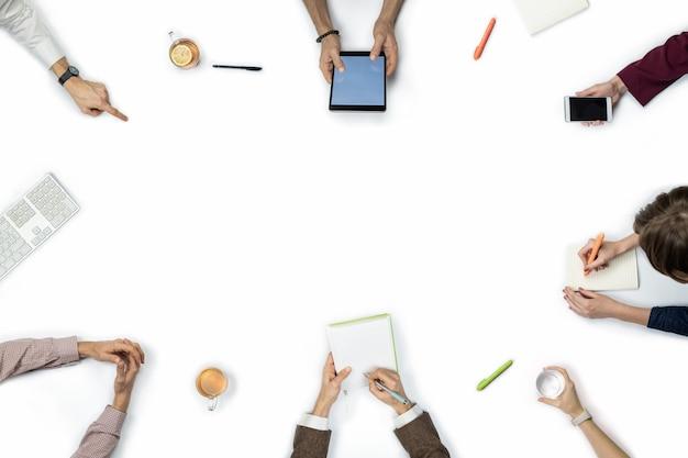 ビジネス会議、トップビューで大勢の人。テーブルの周りの多様な人々の手のコピースペースでフラットレイアウト。