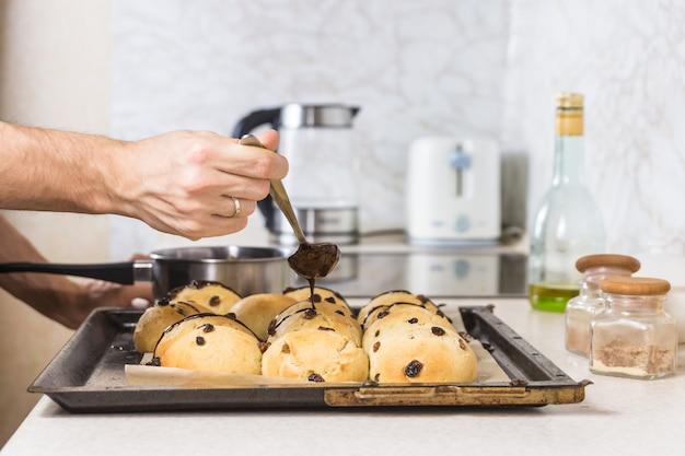 ホットクロスパンを飾る。イースターの甘いパン菓子を味付けする現代の電気炊飯器でチョコレートを溶かす男性の手