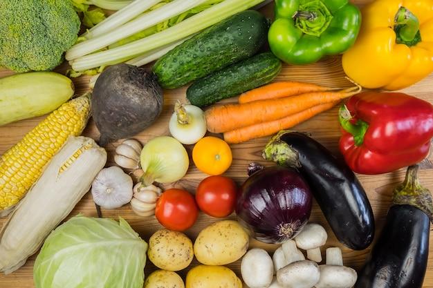 素朴な木のテーブル、トップビューで新鮮な有機野菜。地元産の自然なビーガンフードをテーブルの上に置くフラット